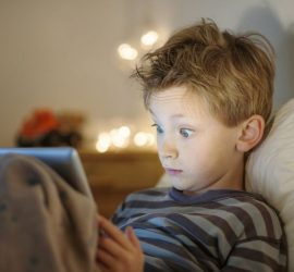 Kid with electronical device in bedroom